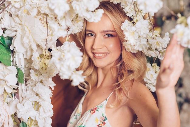 白い美しい花の下で若い女性の笑顔の肖像画