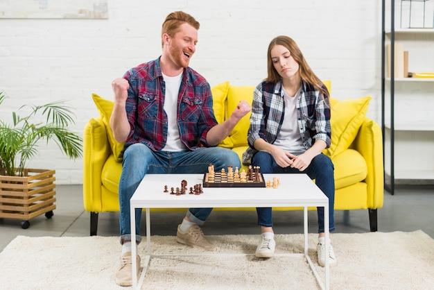 チェスをする彼女の悲しいガールフレンドと一緒に座っている興奮している若い男の肖像