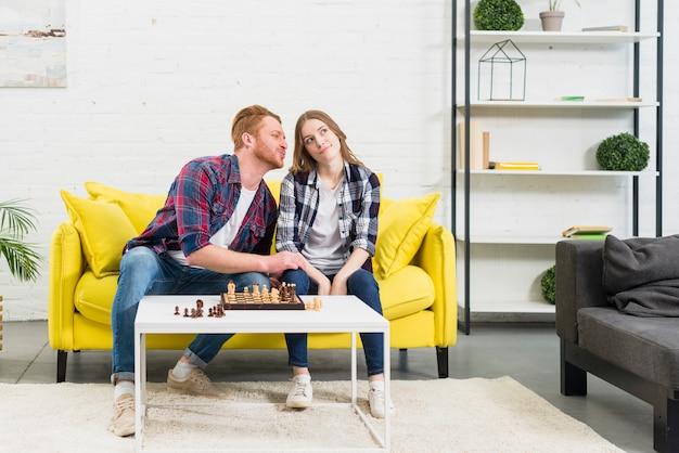 自宅でチェスをしている黄色いソファーに座っていた彼女のガールフレンドを愛する若い男