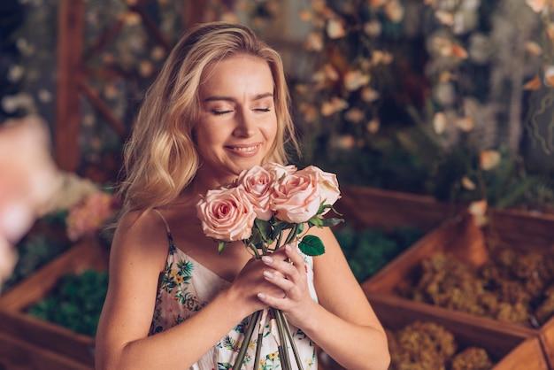 ピンクのバラの臭いがする若い女性のクローズアップ