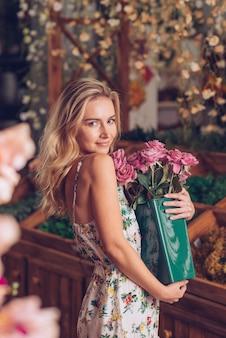 ピンクのバラでいっぱい緑のプラスチック製の容器を保持している金髪の若い女性
