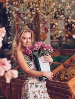 コンテナーにピンクのバラを保持している花柄のドレスの若い女性の笑みを浮かべてください。