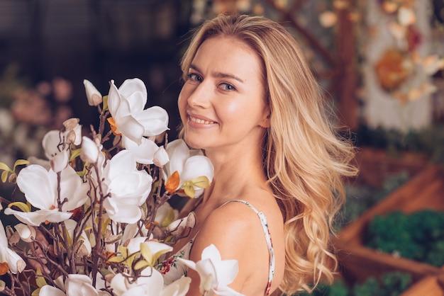 白い美しい花を持つ金髪の若い女性の肖像画を笑顔