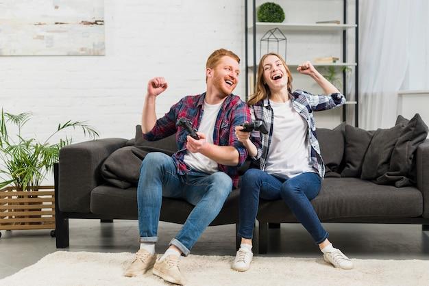 Молодая пара сидит на диване и играет в видеоигру в гостиной