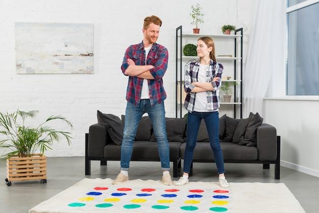 カラードットゲームで遊ぶソファーの前で自信を持って若いカップル立って