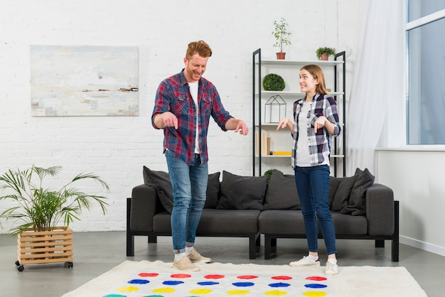 Молодая пара, указывая пальцем на цветную точку игры в гостиной