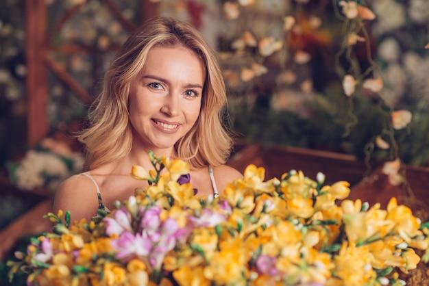 カメラを探している金髪の若い女性の前に黄色の花の花束のクローズアップ