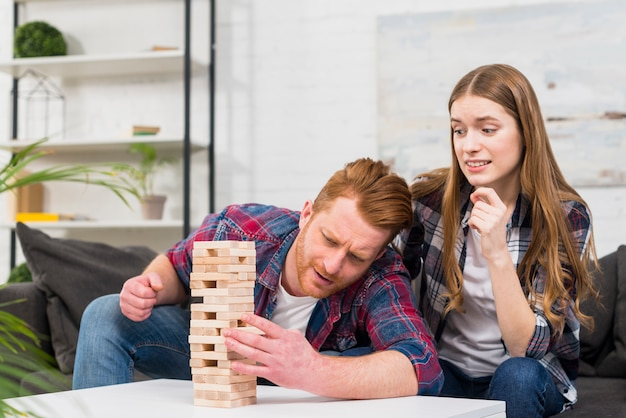 ボーイフレンドを見て笑顔の若い女性がタワーから木製のブロックを削除します