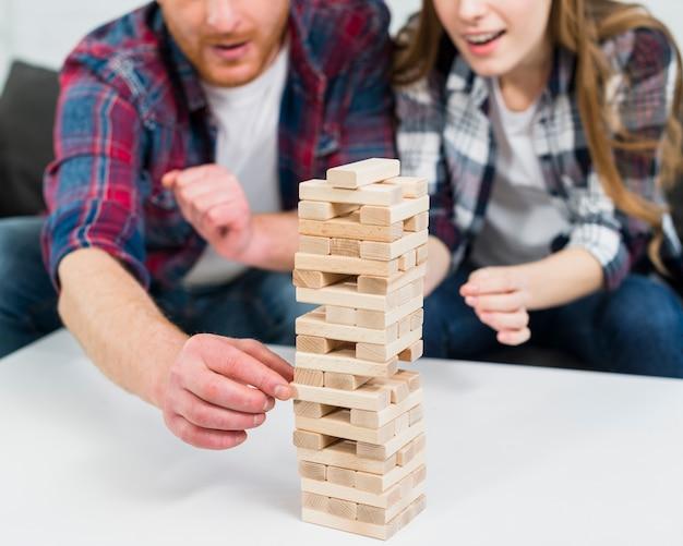 白いテーブルの上の塔から木のブロックを削除する人間の手のクローズアップ