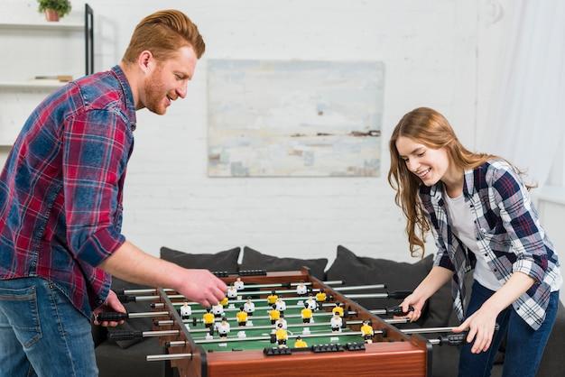 幸せな若いカップルが自宅でサッカーテーブルサッカーゲームをプレイ