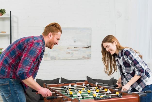 リビングルームでテーブルサッカーの試合を楽しんでいる若いカップルの肖像画を笑顔