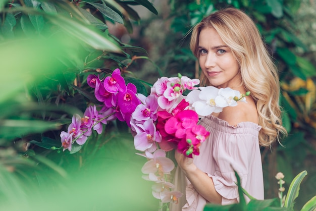 蘭の花を持って庭に立っている金髪の若い女性