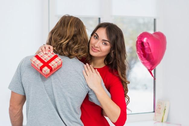 彼女のボーイフレンドを抱きしめる赤いギフトボックスを保持している笑顔の若い女性の肖像画
