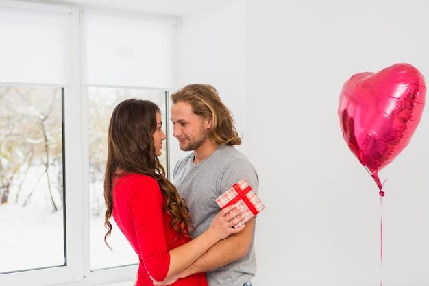ピンクの膨脹可能なハート形バルーン近くに立っている若いカップルを受け入れる