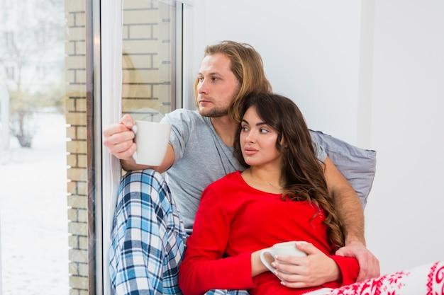 コーヒーのマグカップを保持している窓の近くに座っている若いカップルのクローズアップ