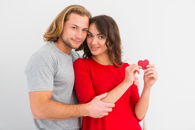 白い背景に対してハート形の紙を見せて彼の笑顔のガールフレンドを抱きしめる金髪の若い男