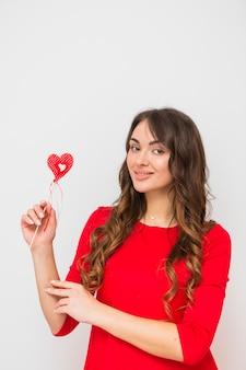白い背景で隔離赤いハートの形を手で押し笑顔の若い女性の肖像画