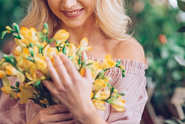 黄色の花の花束と立っている女性