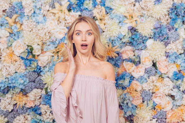 Изумленная женщина стоя на предпосылке цветков