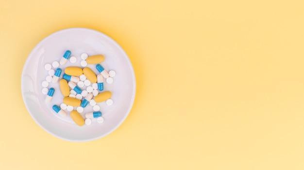 黄色の背景上の白い皿の上の丸薬