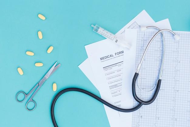 黄色い丸薬。はさみ;聴診器心電図レポート。医療フォームと青い背景上の空の医療注射器