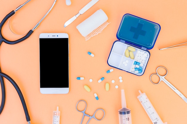 医療ピルボックス。聴診器携帯電話と医療機器のオレンジ色の背景