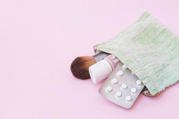 Косметическая кисточка; бутылка лака для ногтей и белая таблетка в блистере внутри хлопкового мешочка на розовом фоне