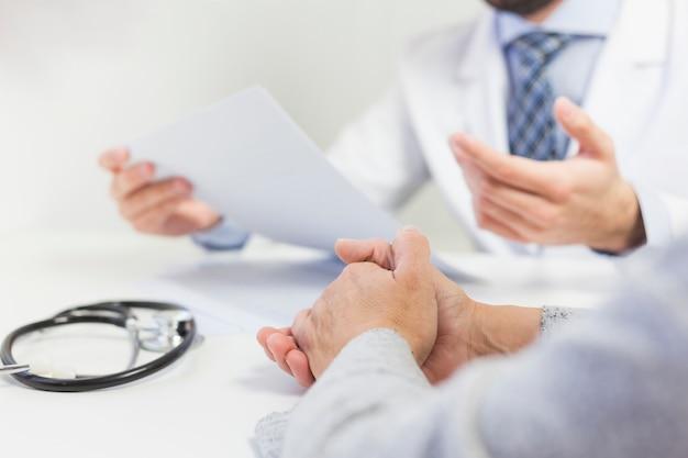 患者と医療報告を議論する彼のオフィスの医者のクローズアップ