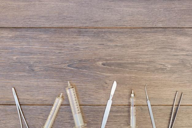 空のプラスチック注射器と木製の机の上の手術器具