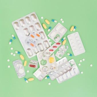 丸薬とブリスターパックの緑色の背景の上から見た図