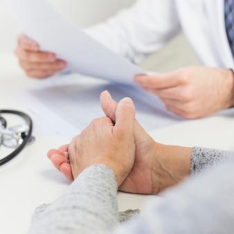 医療報告書を保持している医者のそばに座っているメスの患者のクローズアップ
