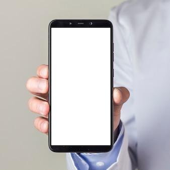 白い画面表示を持つスマートフォンを示す男性医師の手のクローズアップ