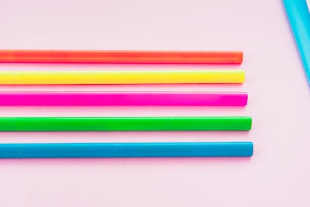 無地の背景に行に配置されたカラフルな鉛筆