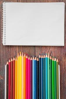 色とりどりの鉛筆と木製の机の上の白いスパイラルメモ帳のクローズアップ