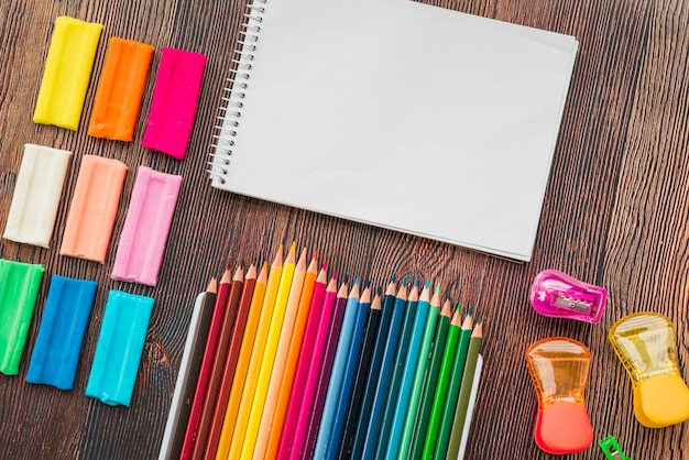 Взгляд высокого угла красочной глины и карандаша с белым спиральным блокнотом