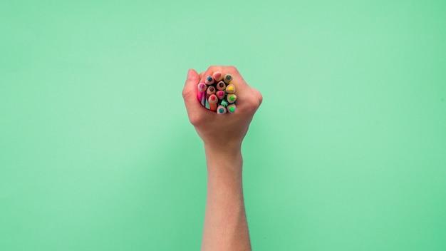 緑色の背景でカラフルな鉛筆のグループを持っている人の手の立面図