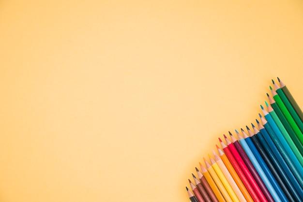 黄色の背景の隅にカラフルな鉛筆の配置