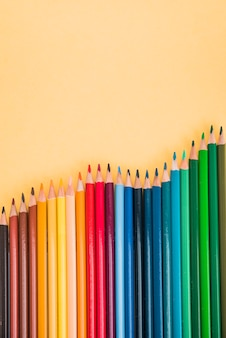 黄色の表面に行に配置されたシームレスなカラフルな鉛筆