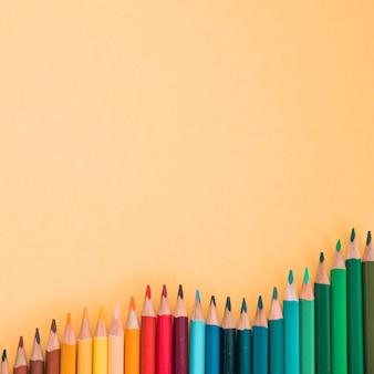 色付きの背景上のカラフルな鉛筆の高角度のビュー