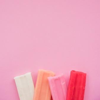ピンクの背景にカラフルな粘土バーのセット