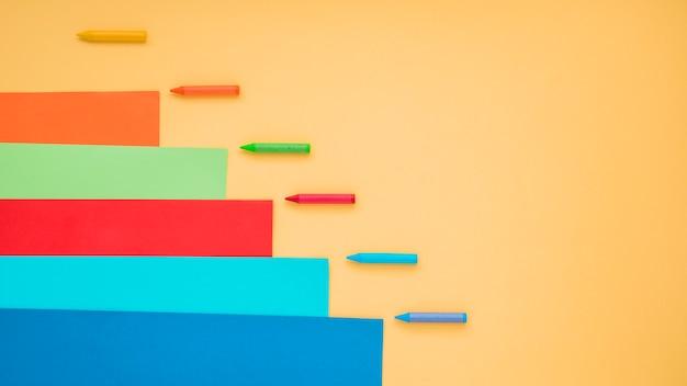 Цветная бумага для карандашей и мелков на желтой поверхности
