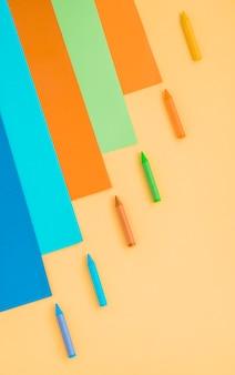 色とりどりの紙とクレヨンのワックス色の高角度のビュー