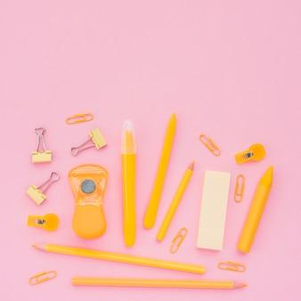 ピンクの背景の上のクローズアップの黄色い学校アクセサリー