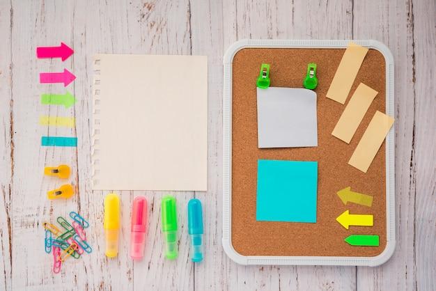 空白の便箋とコルクボード上の接着メモ。蛍光ペンと木製の背景上のペーパークリップ