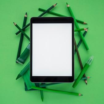 カラー鉛筆の上に空白の画面を持つクローズアップデジタルタブレット。粘土;チューブと濃い緑色の背景上のマーカー
