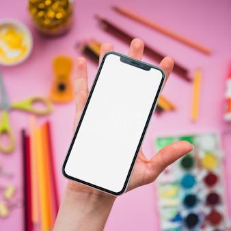 背景にぼやけている文房具の上の人間の手のひらに空白の白い画面を持つ携帯電話