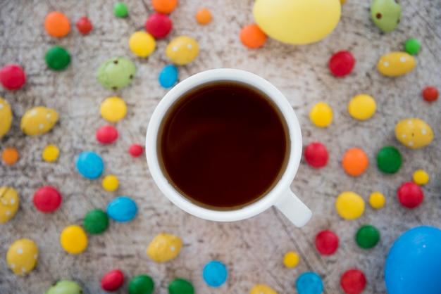 お菓子と卵のミックスの間に飲み物のカップ