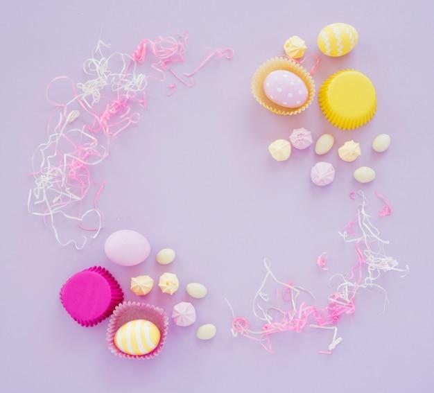 Пасхальные яйца с конфетами на фиолетовом столе