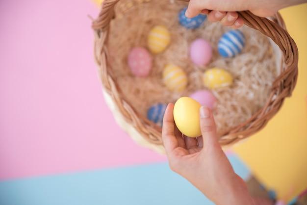 Лицо, занимающее корзину с пасхальными яйцами