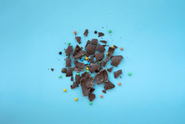 青いテーブルの上の小さなキャンディーとひびの入ったチョコレート